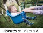 Mom Swinging Baby Girl In Swing