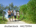 family walking from the beach talking and giggling - stock photo
