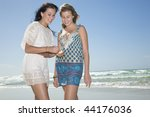 sisters looking at shell on beach - stock photo