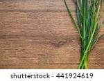 Small photo of A bunch of fresh spring green grass on a wooden background. Old wooden texture with terrestrial plants. Land plants. Plant with green stems and low, components for preparation salad. Vegetarian food
