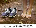 Small photo of bare feet stay tiptoe and trainer shoes close up photo on the forest path