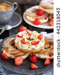 Small photo of Cream puff rings (choux pastry) decorated with fresh strawberry and caramel sauce