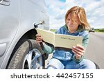 Small photo of Woman reading owner's manual of her car