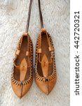 Small photo of Pair of traditional Bulgarian leather shoes against white lambskin background
