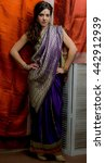 Small photo of The young dark-haired woman in the rich Indian saris standing akimbo on the background screen decorated with bright silk. Indian style.