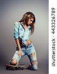 Small photo of Attractive girl alluring with her skateboard. Studio shot.