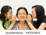 two granddaughter whispering some news to their old grandmother - stock photo