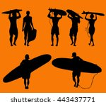 set of silhouette surfers over...
