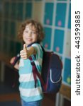 Small photo of Elementary school student standing near lockers in school hallway. Behind kid's school backpack. The boy has blond curly hair and blue eyes. With a gesture he showed that he's all right.