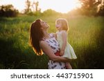 mom kisses and hugs daughter on ... | Shutterstock . vector #443715901