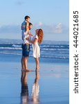 Small photo of Happy full family - father, mother, baby son walk with fun along edge of sunset sea surf on black sand beach. Active parents and people outdoor activity on summer holiday with children on Bali island