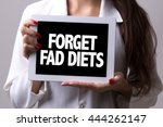 Small photo of Female doctor holding a tablet with the text: Forget Fad Diets
