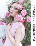 Stock photo beautiful sexy girl in a pink dress standing in the garden roses in a sunny bright summer day with 444505279