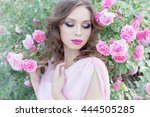 Stock photo beautiful sexy girl in a pink dress standing in the garden roses in a sunny bright summer day with 444505285