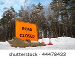 fluorescent road sign on a snow covered highway - stock photo