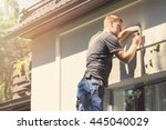 electrician installing lamp on... | Shutterstock . vector #445040029
