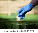 Water sample. Hand in glove collects water in a test tube. Concept - water purity analysis, environment, ecology. Water testing for infections, permission to swim