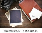 Small photo of Album with vintage photos and camera on wooden background