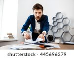 Small photo of Absentminded young businessman rummaging in papers, office background.