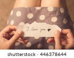 Stock photo top view of woman in dotted dress holding a paper message with the text i love you 446378644