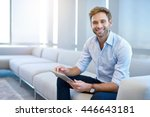 Small photo of Portrait of a handsome young businessman sitting on a modern couch, holding a digital tablet, and smiling broadly at the camera