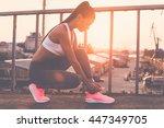 tying her shoelaces. beautiful...   Shutterstock . vector #447349705