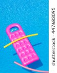 Small photo of Pink air bed and yellow tube floating on a swimming pool