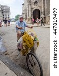 Small photo of HAVANA, CUBA - JUNE 19, 2016: Old man on a bicycle near Plaza Vieja is transporting two bags of aluminum cans he will sell to supplement his meager pension from the Cuban government.