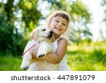 Stock photo little girl with a golden retriever puppy a puppy in the hands of a girl 447891079