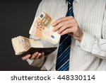 Businessman Putting Banknotes...