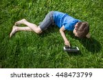 child is lying on the grass... | Shutterstock . vector #448473799