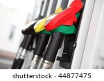 Several gasoline pump nozzles at petrol station - stock photo
