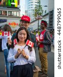 Small photo of TORONTO,CANADA-JULY 1,2016:Canada Day people: Asian couple enjoying the music and events in Dundas Square.Canada Day is the national day of Canada and a federal statutory holiday