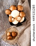 Small photo of Fresh whole white mushrooms, or agaricus, in a bowl on a rustic wooden counter ready to be cleaned and washed for dinner, overhead view