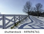 Small photo of Long path of triangular shadows on snow by wooden fence at the edge of an equestrian farm on a sunny afternoon in January, northern Illinois, USA, for seasonal and recreational themes