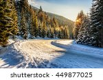 winter mountain landscape. winding road that leads into the spruce forest covered with snow at sunrise - stock photo
