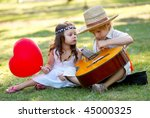 Young Couple With Guitar On...