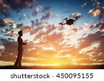 man operating a drone at sunset ... | Shutterstock . vector #450095155