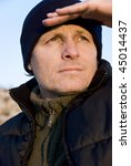 Small photo of A colour portrait photo of an outdoor man wearing a bodywarmer and hat with stubble on his face