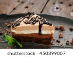 Peace of layered souffle dessert with chocolate sauce on black plate with mint leaves, on blurred wooden table