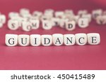 Small photo of Guidance word written on wood cube with red background