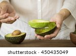 Stock photo woman use a spoon to scoop the avocado out of the shell 450435049