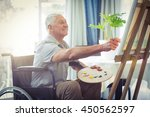 happy senior man painting at... | Shutterstock . vector #450562597