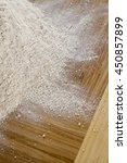 Small photo of spread of whole wheat flout on a wood cutting board