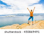 Small photo of Woman hiker hiking with backpack, arms outstretched looking at sea and mountains view. Accomplished climber with hands up outdoors. Beautiful inspirational landscape. Trekking and activity concept.