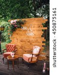 Small photo of Wedding. Banquet. Vintage photo zone decorated by Mr. & Mrs. signs and old chairs and table. Vertical shot.