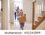 family carrying boxes into new... | Shutterstock . vector #451241899
