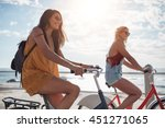 female cyclist rides along the... | Shutterstock . vector #451271065