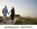 Couple Walk Hand In Hand On A...
