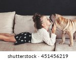 Stock photo home portrait of cute child kissing puppy of chinese shar pei dog on the sofa against black wall 451456219